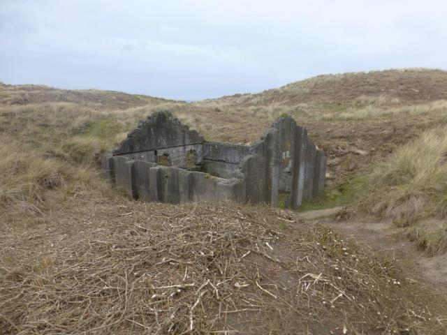 One of four surviving roofless structures thought to be the earliest known surviving group of mass-concrete magazines, dating to the 1890s.