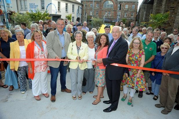 The mayor of Hayle Nick Farrar and president of the Hayle Branch of the RNLI Pauline Marks (centre) watched by members of the community cut the ribbon to officially re-open the Isis gardens in Foundry Square in Hayle